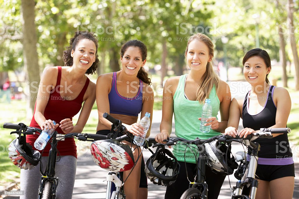 Four women posing with their bikes while resting royalty-free stock photo