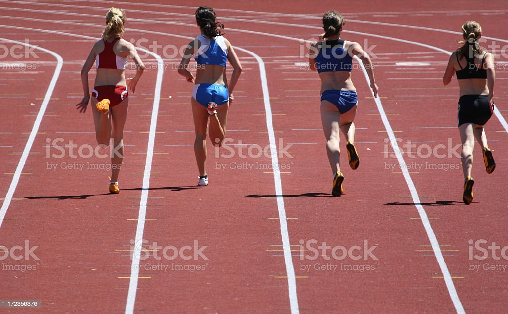 Four women running the hundred meter race on a track stock photo