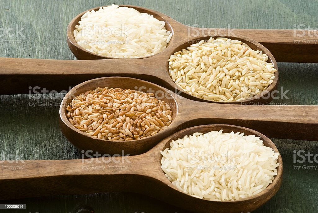 Four wooden spoons holding different types of rice stock photo