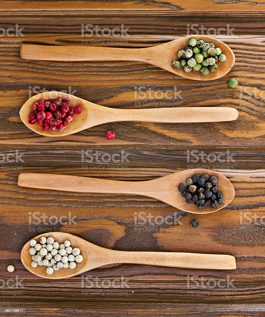 Four wooden spoons with color peppers royalty-free stock photo