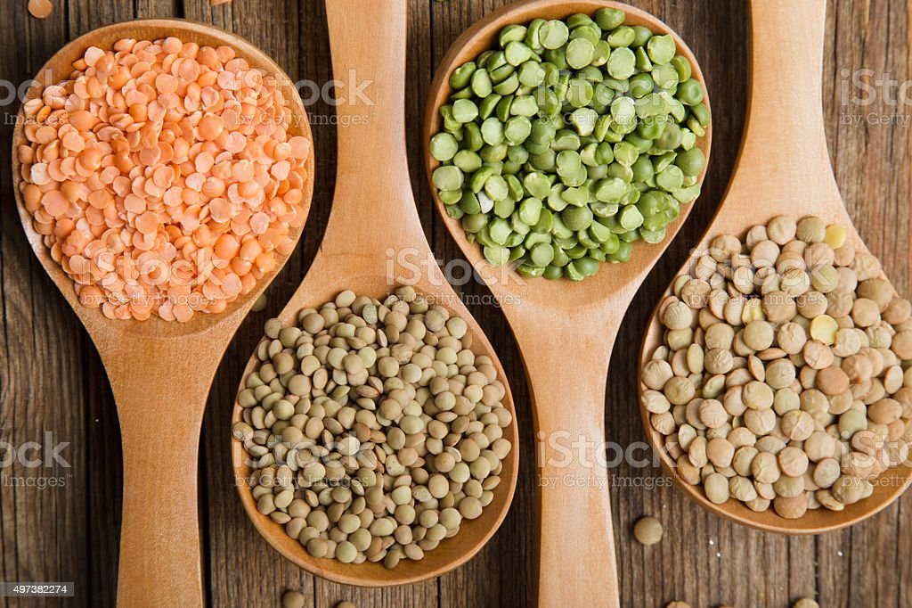 Four wooden spoons with dried peas and lentils stock photo