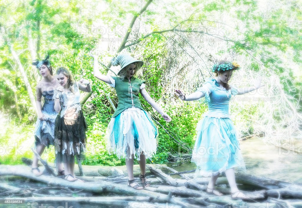 Four Woodland Fairies Crossing Mystical Stream stock photo