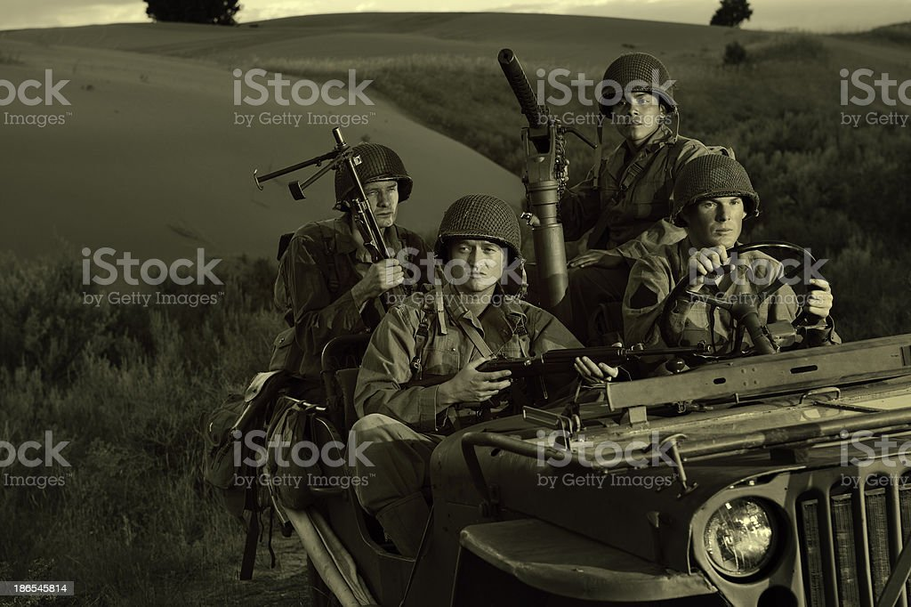Four WWII Soldiers Riding In A Jeep At Days End royalty-free stock photo