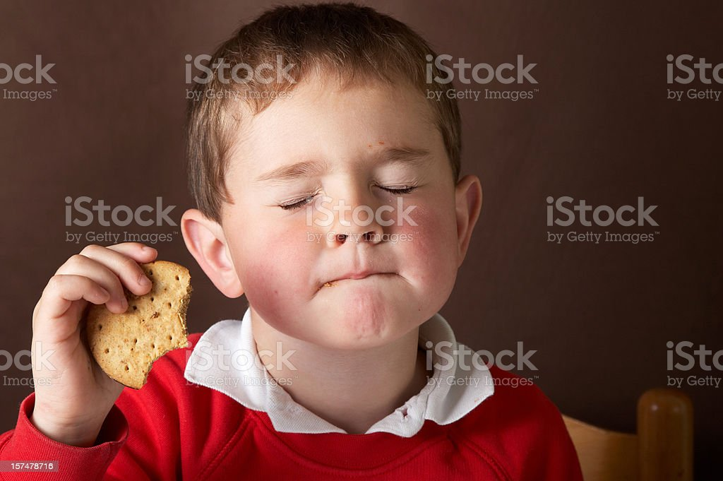Four year old boy eating chocolate biscuit stock photo