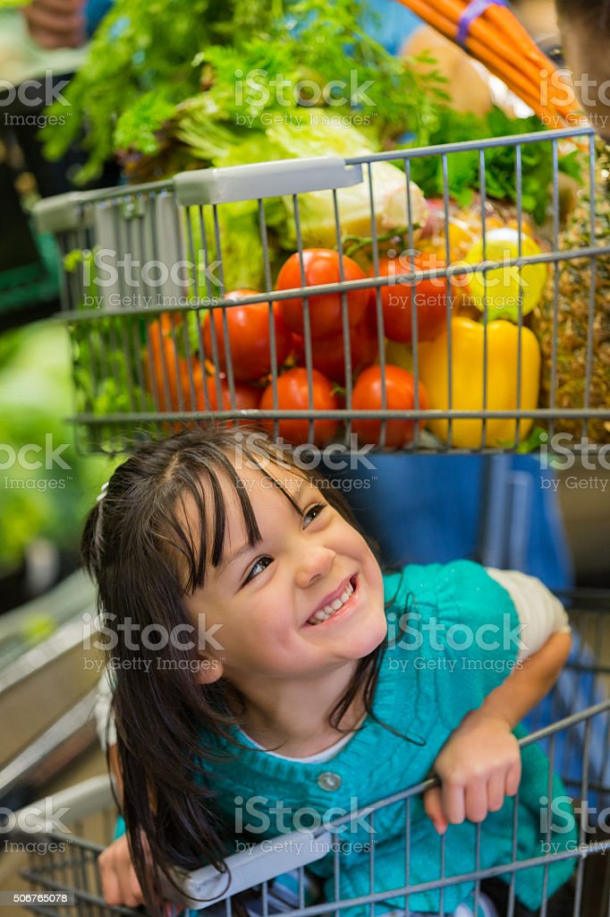 Four year old Hispanic girl shopping for groceries with family stock photo