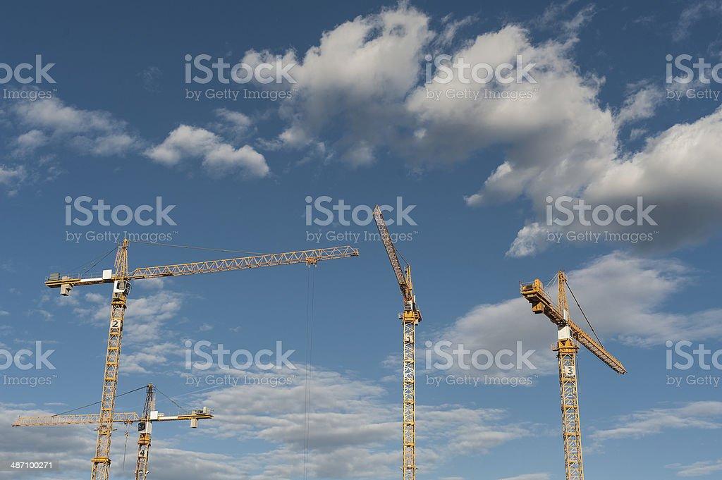 Four yellow building cranes stock photo