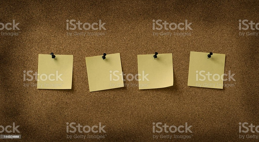 four yellow notes pinned to grunge cork background royalty-free stock photo
