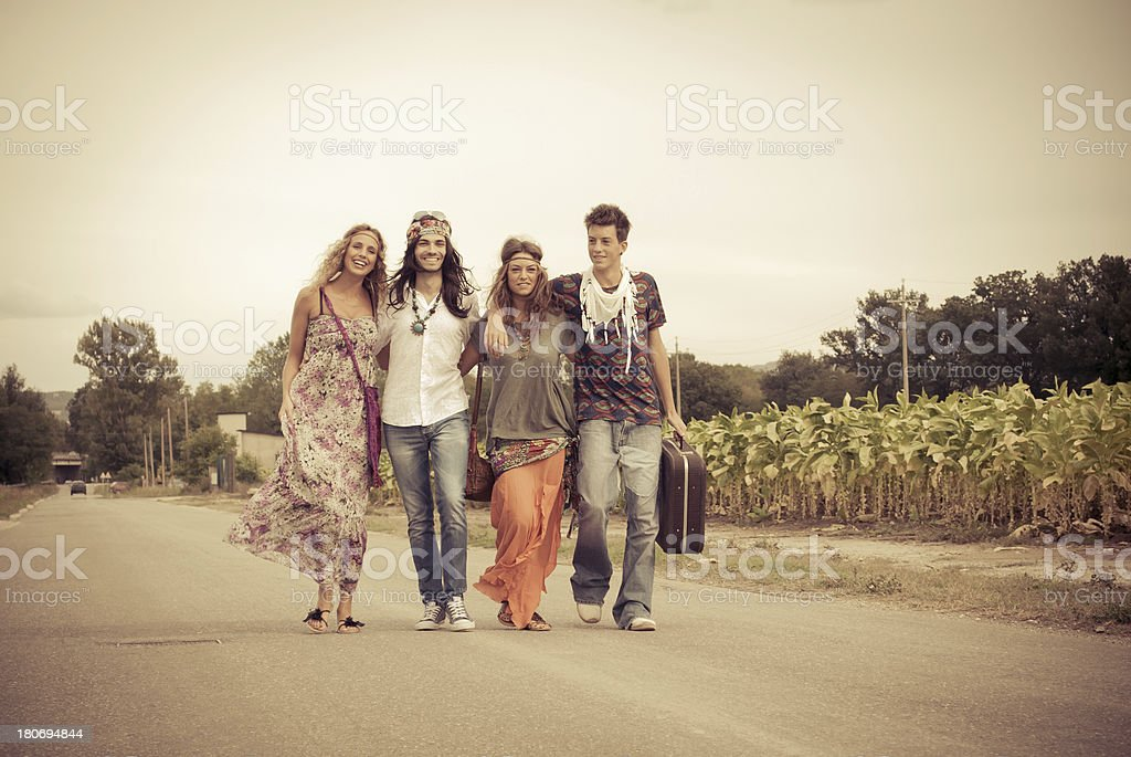 Four young adult hippie friends smiling and walking on countryside stock photo