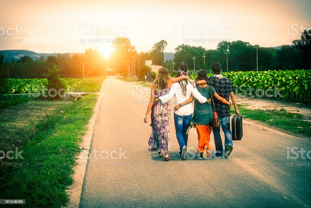 Four young adult hippie friends walking on countryside against sunset stock photo