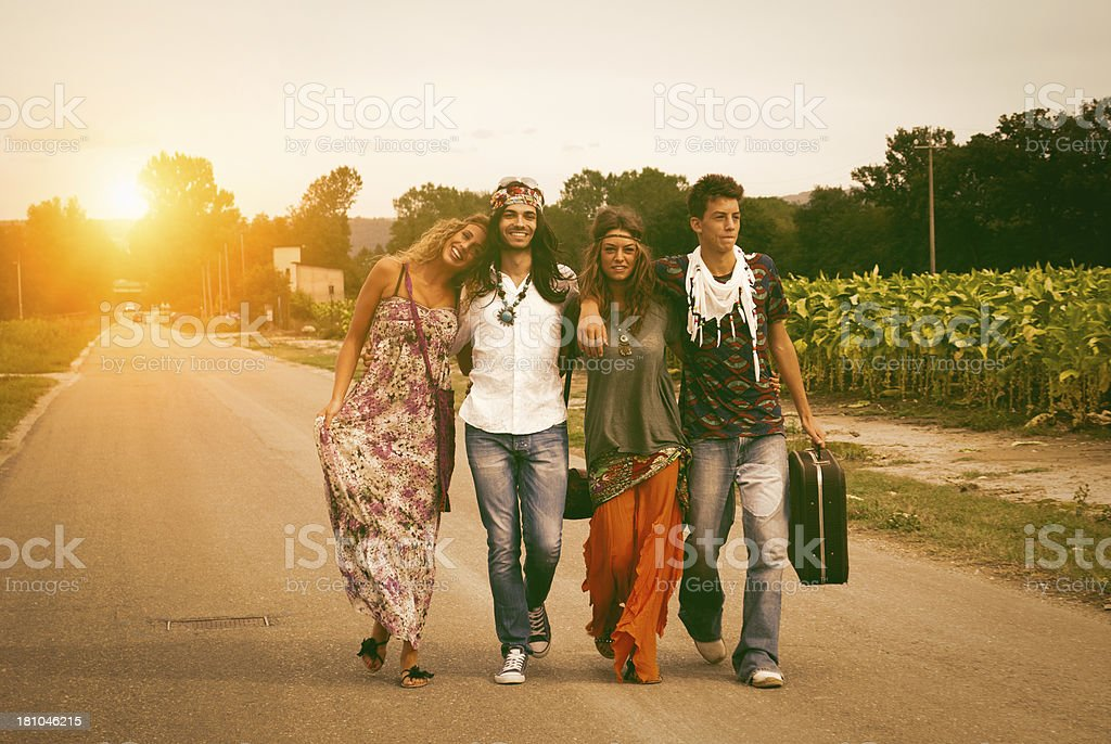 Four young adult hippie friends walking on countryside royalty-free stock photo