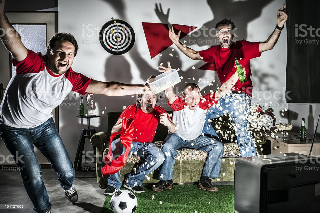 Four young adult men friends watching football on television: Goal! stock photo