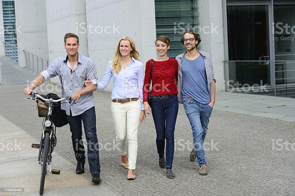Four young adult walking talking having fun royalty-free stock photo