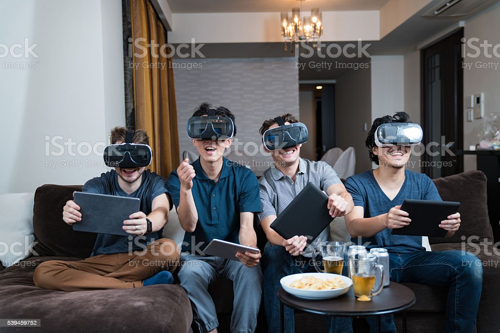 Four young adults trying out some virtual reality headsets stock photo