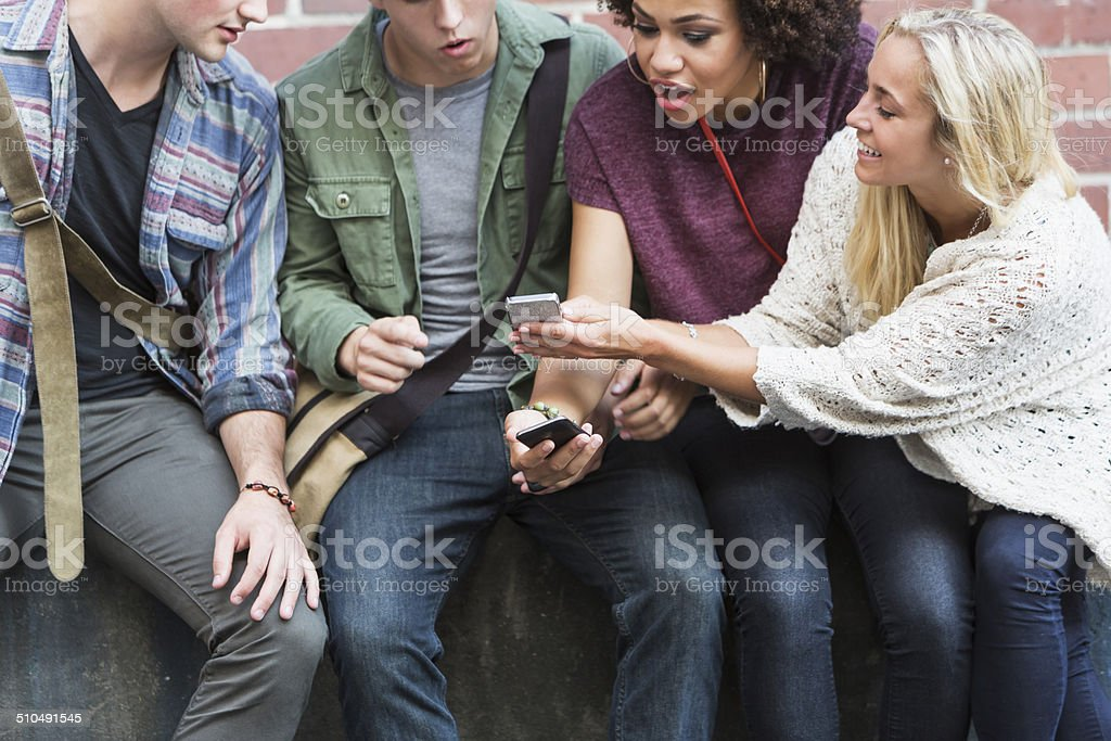 Four young adults with mobile phones stock photo