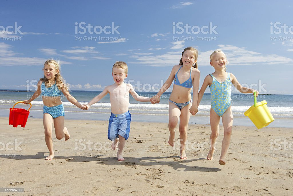 Four young children playing on the beach royalty-free stock photo