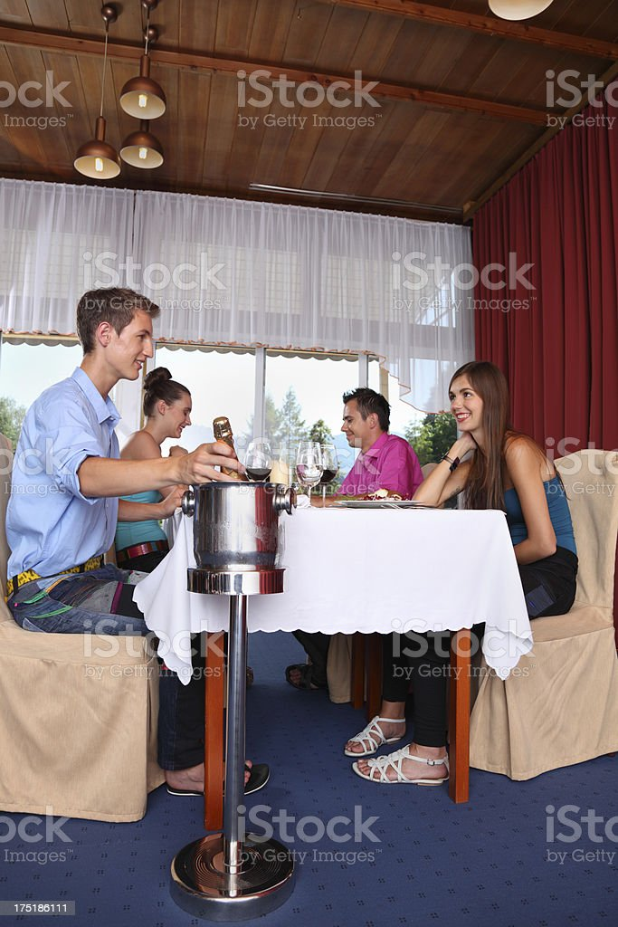 four young friends enjoy champagne meal in stylish room royalty-free stock photo