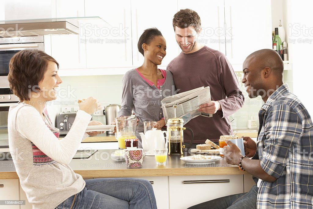 Four young friends gather together in kitchen for breakfast royalty-free stock photo