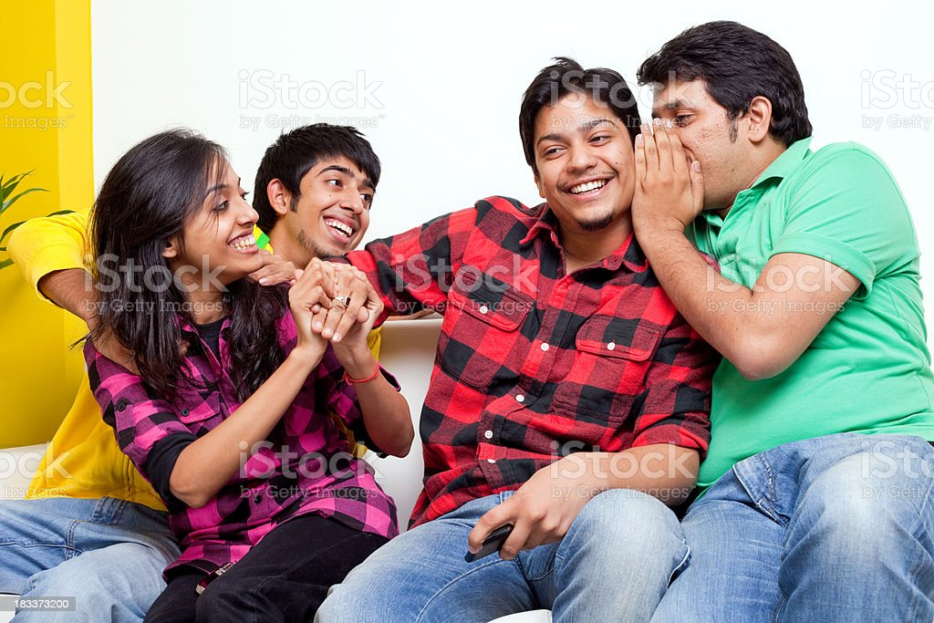 Four Young Indian Cheerful Friends Gossip Whispering on Sofa royalty-free stock photo