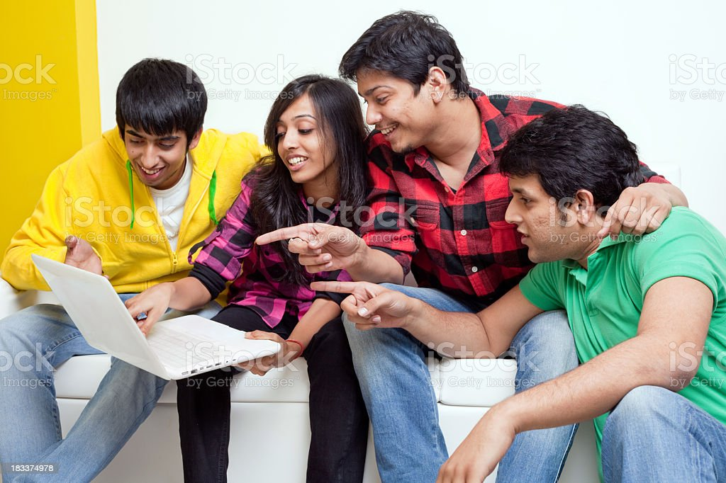 Four Young Indian Cheerful Friends looking at Laptop sitting Sof royalty-free stock photo