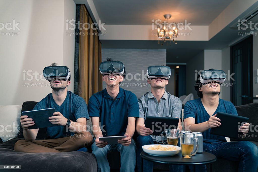 Four young men trying out some virtual reality headsets stock photo