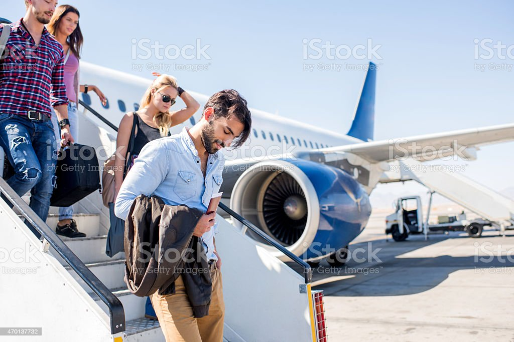 Four young people disembarking the airplane. stock photo