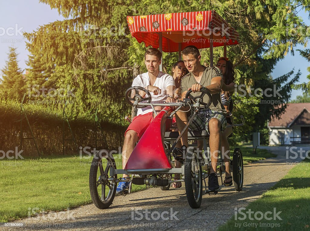 Four young people in a four-wheeled bicycle stock photo