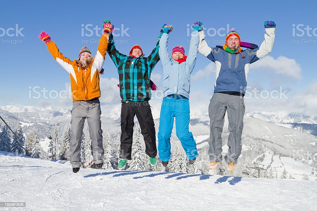 Four young people in winter clothes jumping on snow royalty-free stock photo