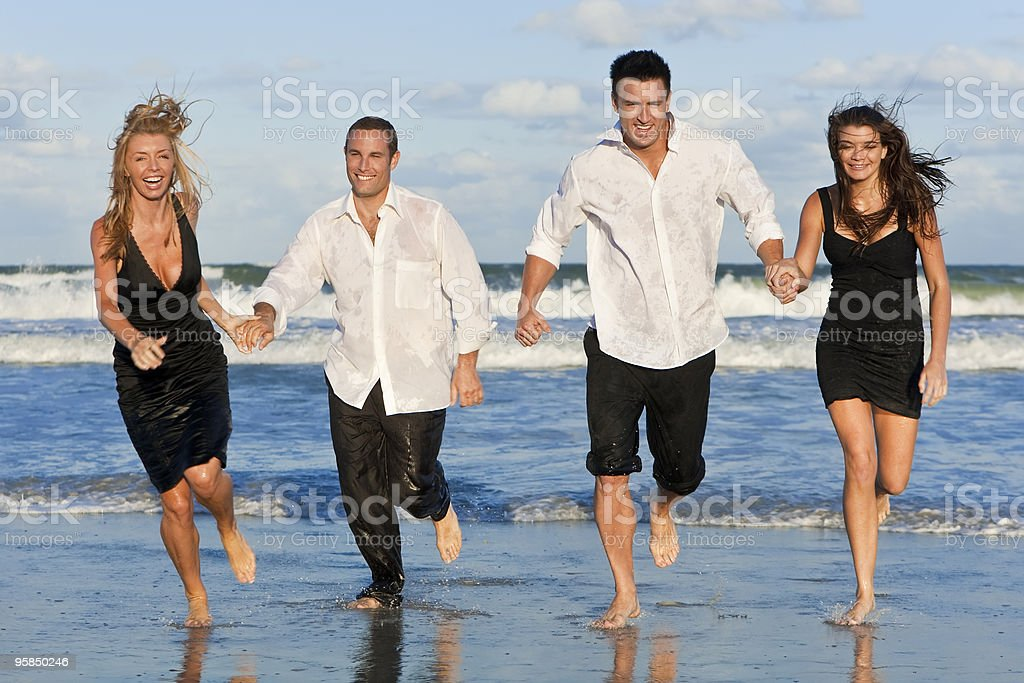 Four Young People, Two Couples, Having Fun Running On Beach royalty-free stock photo