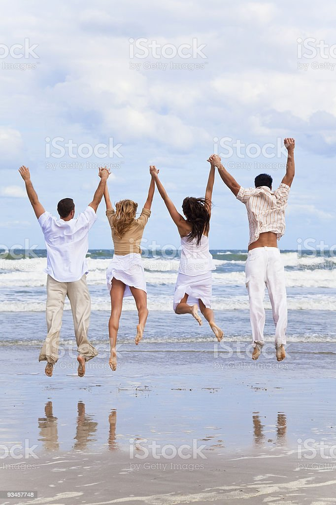 Four Young People, Two Couples, Jumping in Celebration On Beach royalty-free stock photo