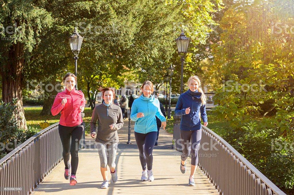 Four young women jogging over bridge stock photo
