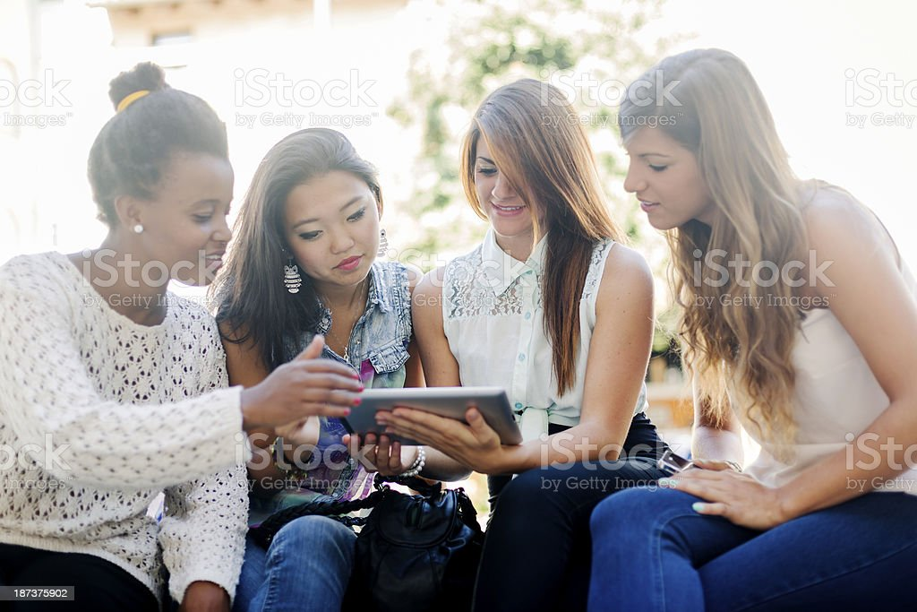 Four young women using a digital tablet royalty-free stock photo