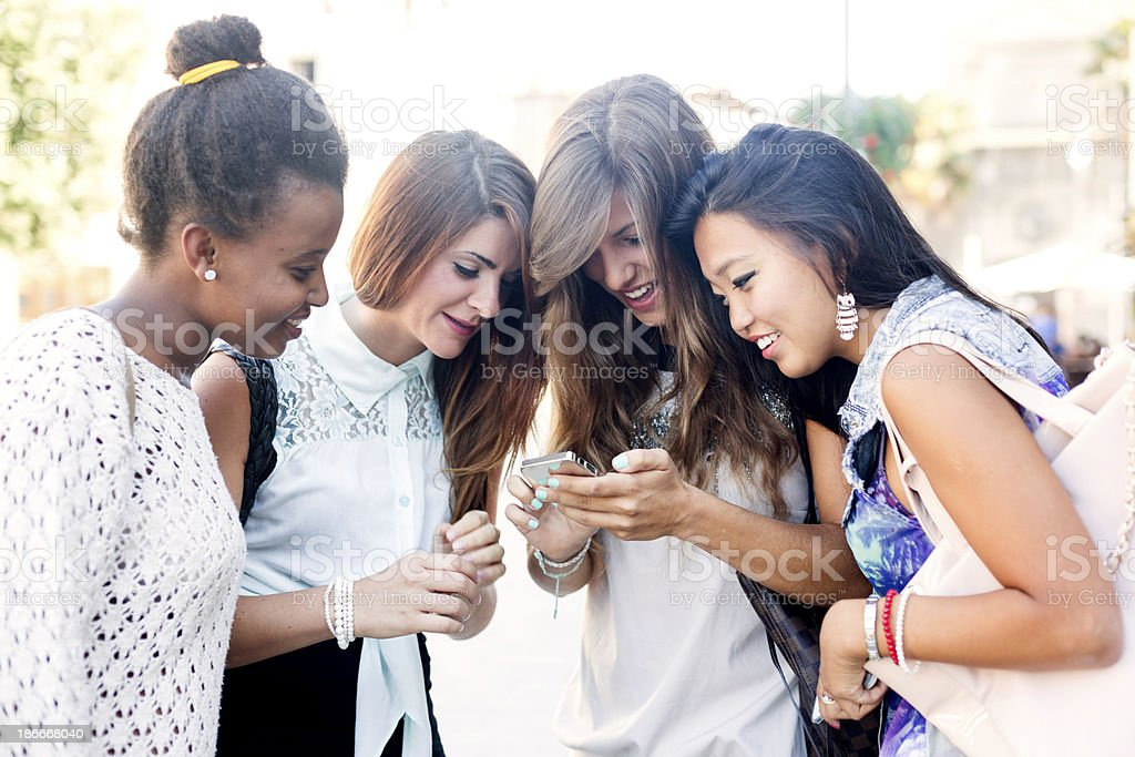 Four young women using a smartphone royalty-free stock photo
