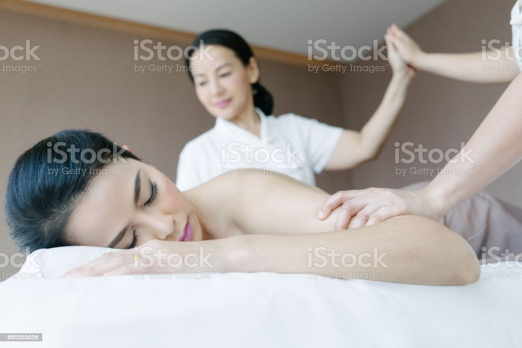 Four-hands aromatherapy warm oil massage stock photo