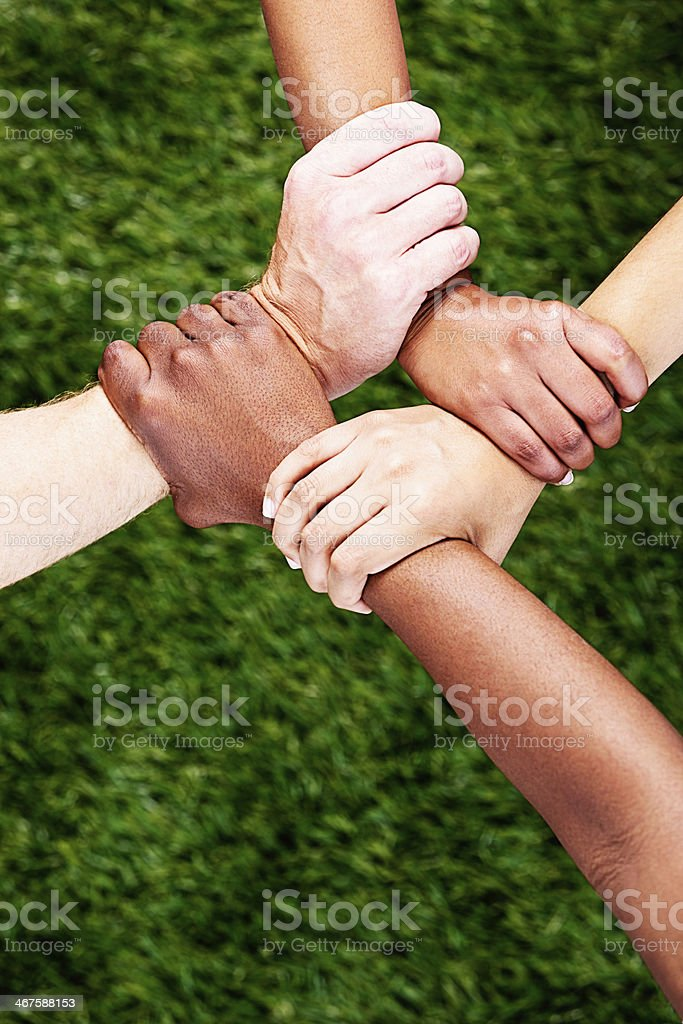 Four-part harmony; quartet of linked, clasped hands stock photo