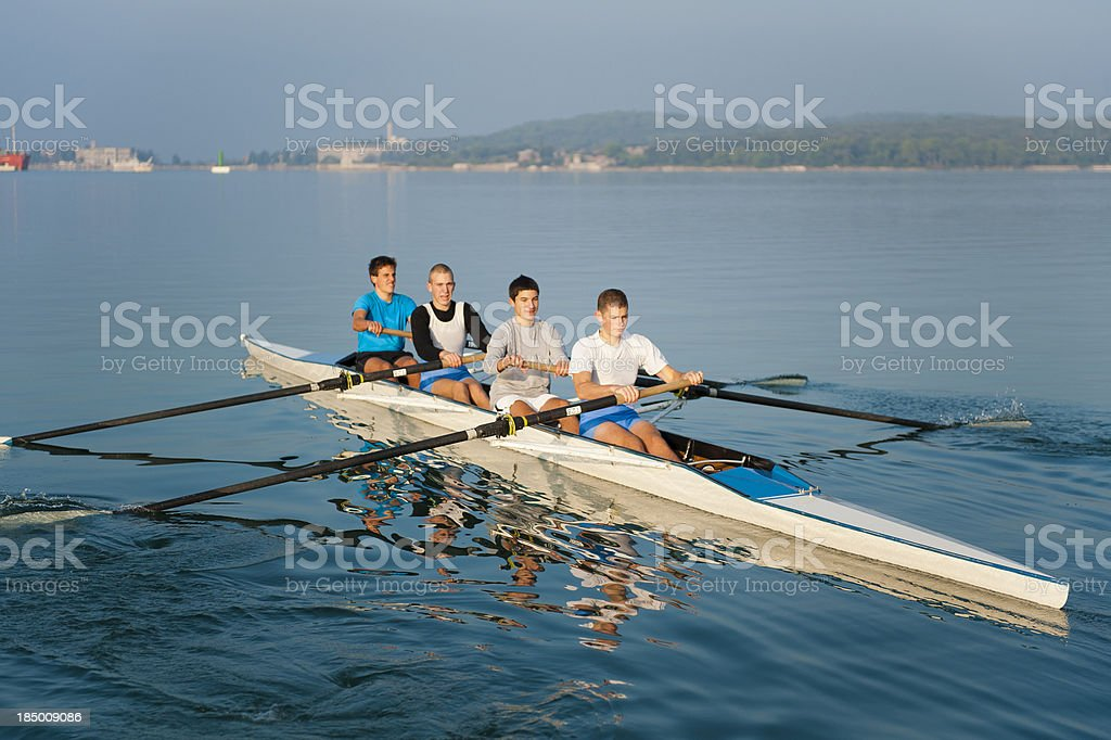 Four-seated scull rowing team practicing stock photo