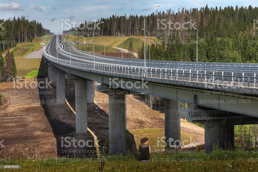 Four-speed road through forest, and steel motor road bridge. stock photo