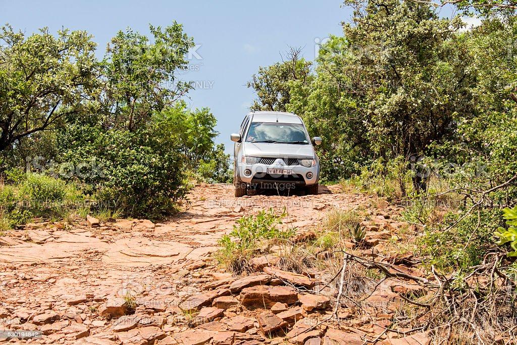 Four-wheel drive vehicle Mitsubishi Triton is doing off- road. stock photo