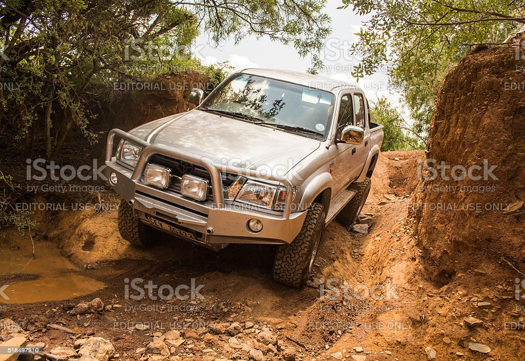 Four-wheel drive vehicle Toyota Hilux is doing off-road trail. stock photo