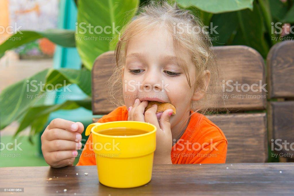 Four-year girl funny stuffed bun in his mouth stock photo
