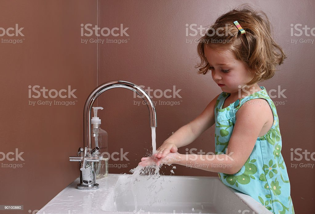 Four-year-old girl washing hands.  stock photo