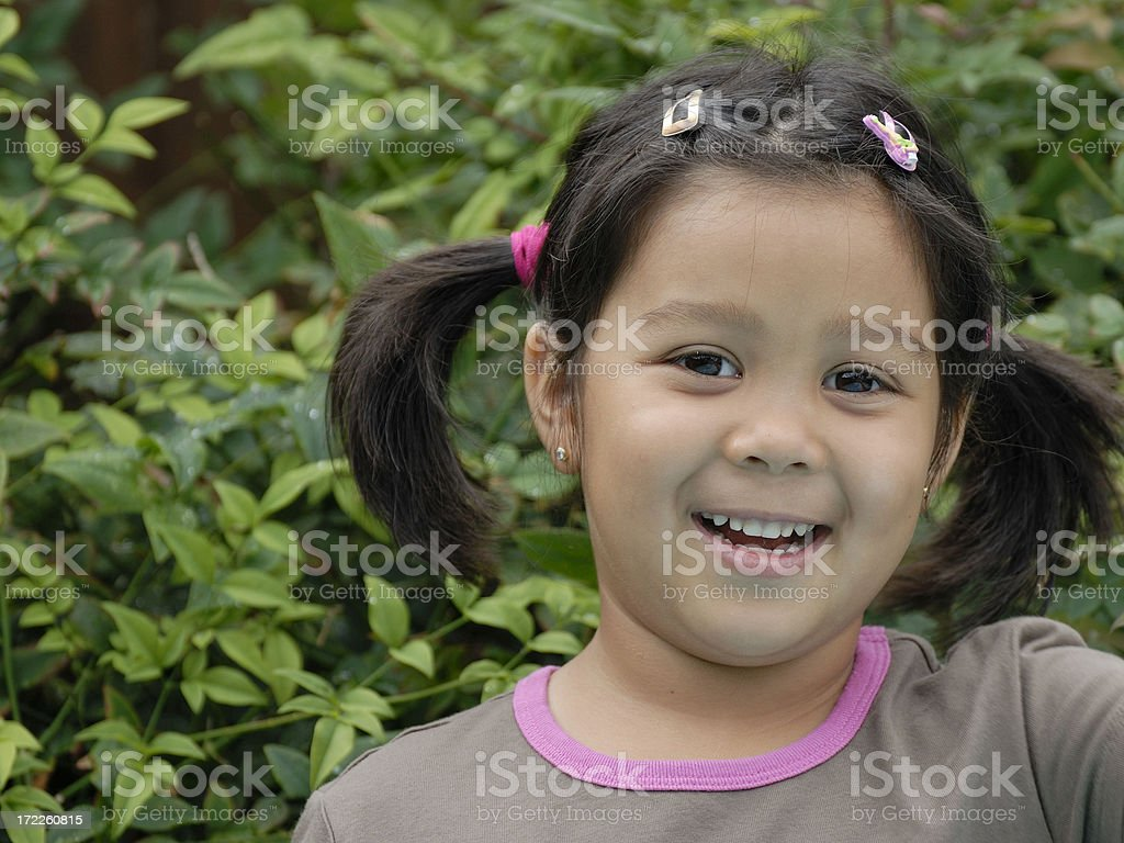 Four-year-old smiling against bushes royalty-free stock photo