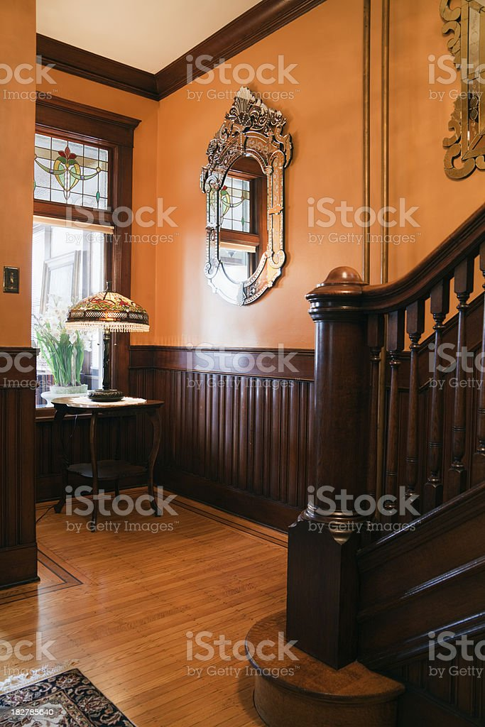 Foyer with Wainscoting, Wooden Stairway in Restored Ornate Victorian Home stock photo