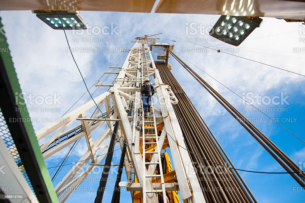 Fracking rig workers climb main drill tower. stock photo