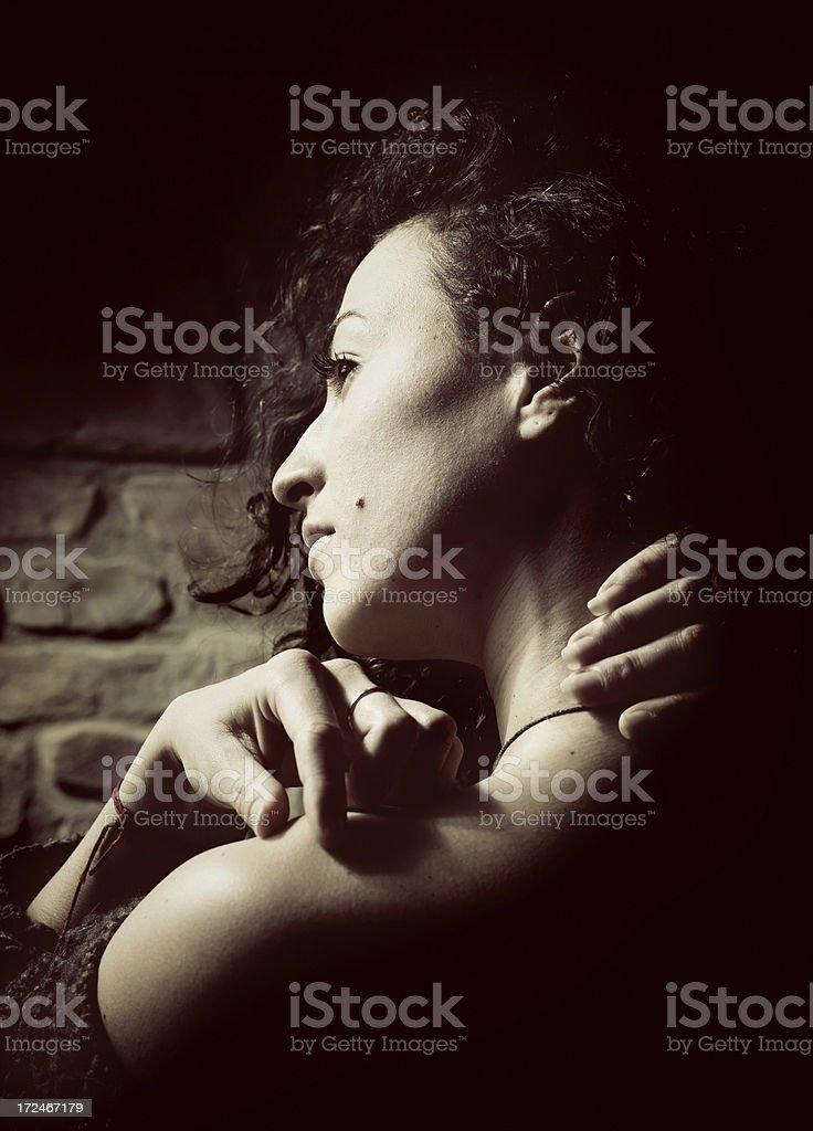 Fragile girl on dark. Low light to create a dramatic scene.