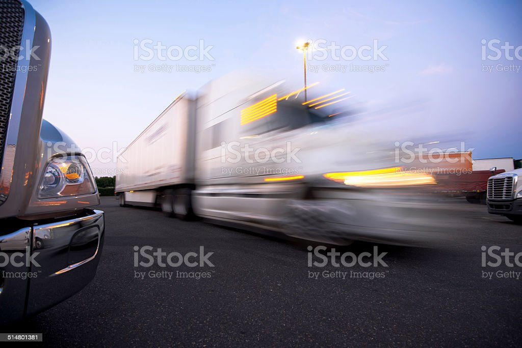 Fragment modern trucks on trakstope against moving truck with headlights stock photo