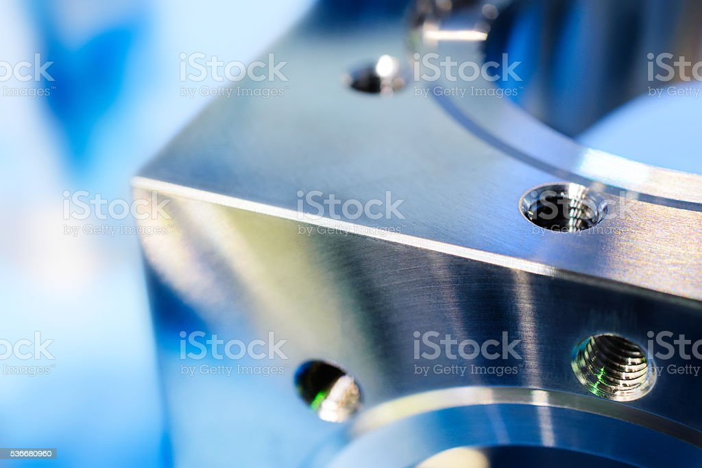 Fragment of a metal cube with holes and metric thread. stock photo