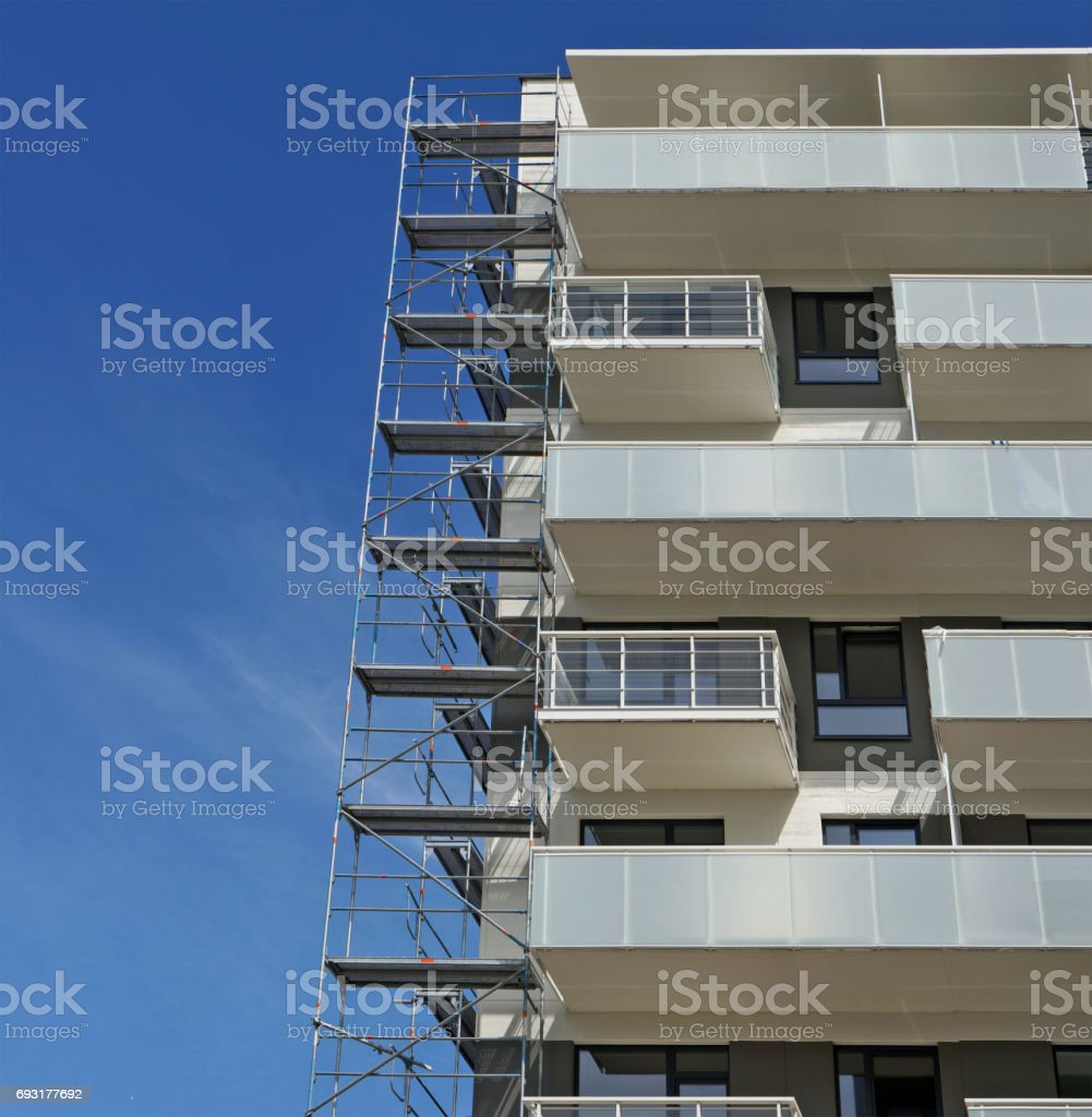 Fragment of a new inhabited apartment house and metal building constructions against the background of the blue summer sky stock photo