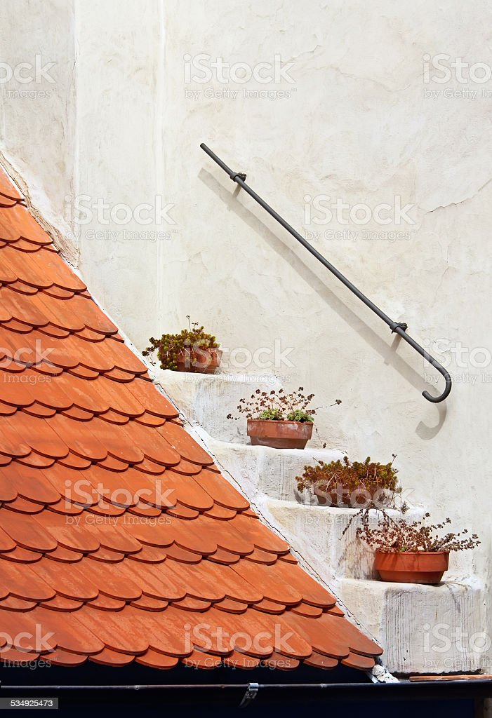 Fragment of a red roof on white wall background stock photo