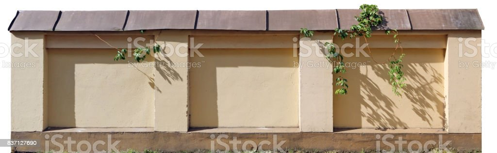 A fragment of a renovated old stone fence. The surface is plastered, a coating of new metal tiles. stock photo