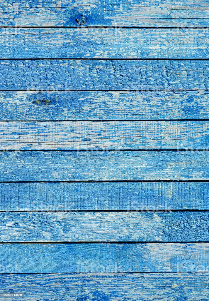 Fragment of an old fence. Cracked azure paint texture. Light blue wooden planks background. stock photo